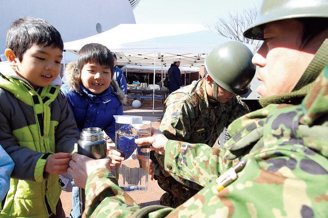 画像: 福島県の避難所で給水支援を行う隊員と子どもたち(写真:朝雲新聞/時事)