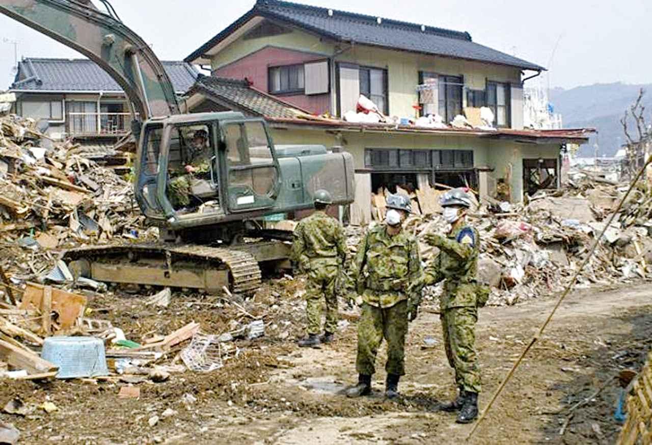 画像: 東日本大震災では写真のような現場で小隊長として捜索活動の指揮を執った吉本3佐。余震の不安が残る中、がれき撤去や行方不明者の捜索を行った