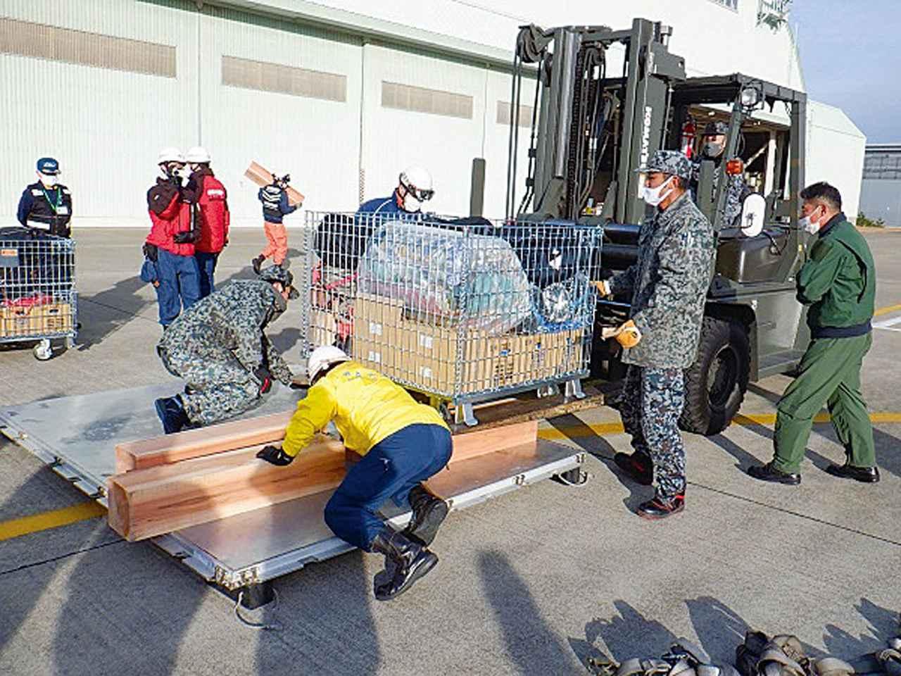 画像: 緊急消防援助隊輸送訓練で、災害救助に必要な物資の搭載準備を行う空自隊員と消防隊員