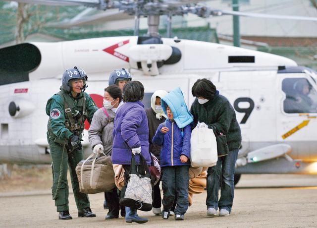 画像: 宮城県気仙沼市で海上自衛隊のヘリコプターによって救助された被災者(写真:EPA=時事)
