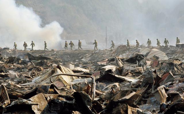 画像: 岩手県大槌町で焼け野原となった被災地を捜索する隊員(写真:時事)