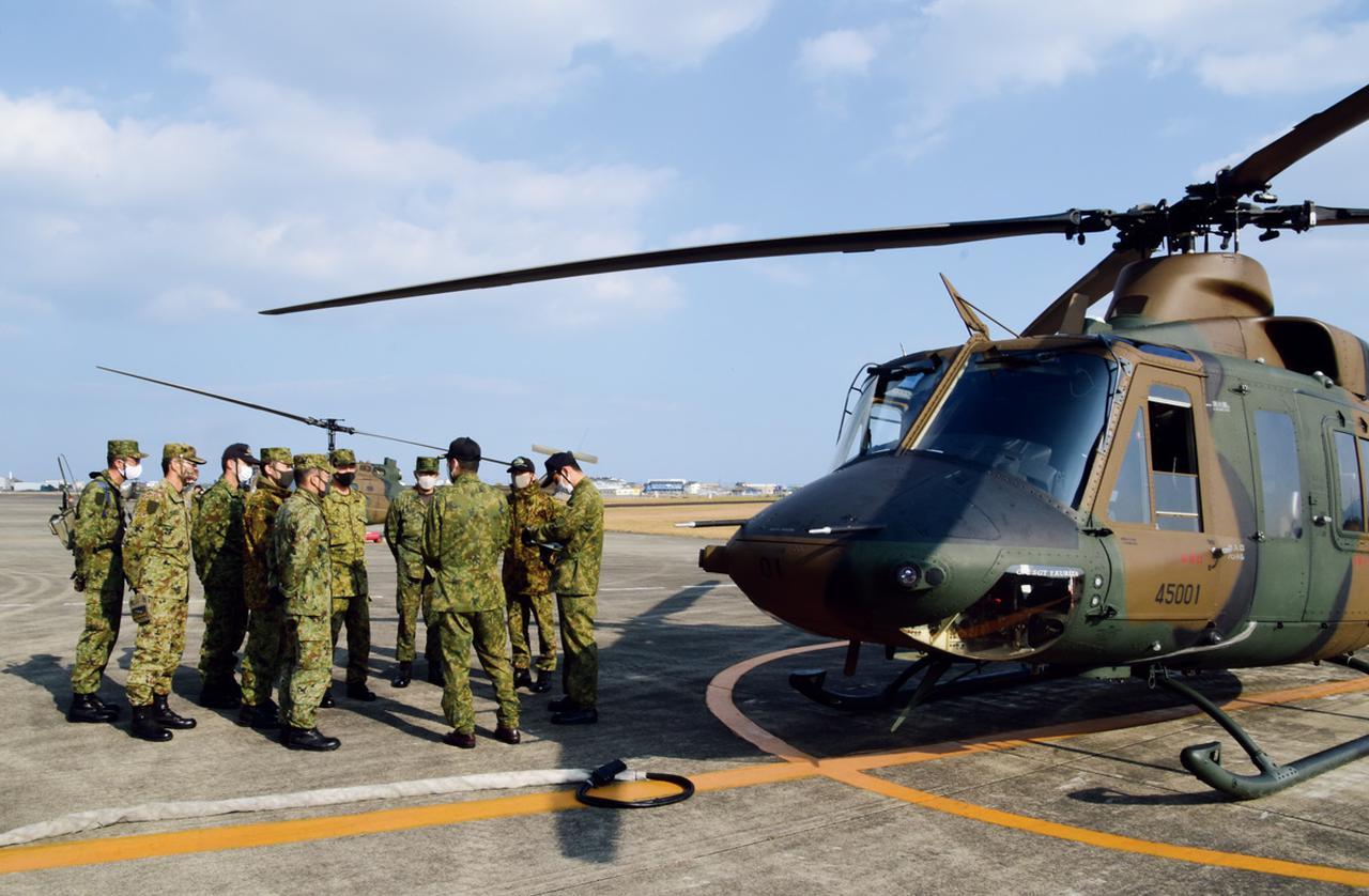 画像: 飛行試験前のUH-X試験機のそばで最終チェックを行う、担当パイロットや整備員たち。機体の状態や進捗状況などをあらためて確認していく