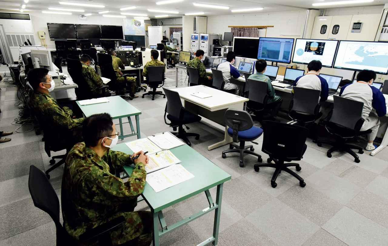 画像: モニター室にて、飛行中の試験機から送信される各種データをモニタリングする隊員たち。取材時のUH-X飛行試験では、メーカーから派遣された技師も参加していた