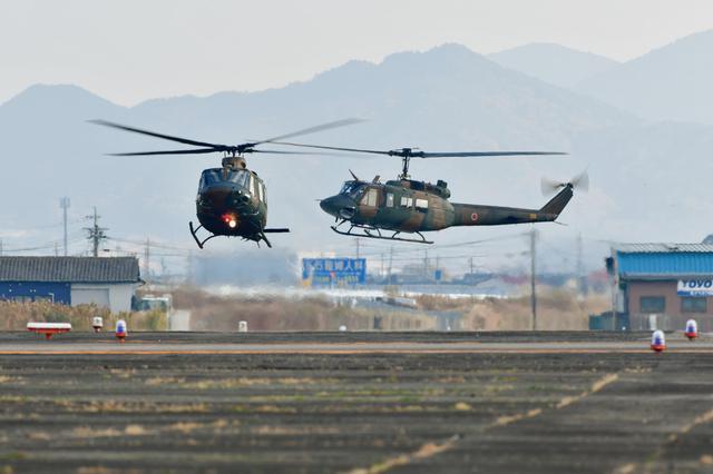 画像: 今まさに試験飛行へと飛び立つUH-X試作機(左)と、試験のサポートを行うため追従して飛び立つUH-1J(※)。新旧そろい踏みの珍しいシーン。UH-X試作機のローターブレードは従来の2枚羽根から4枚羽根に変更されている