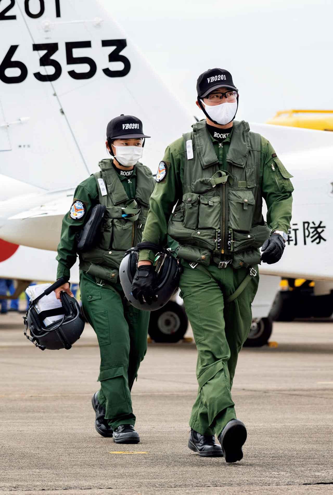 画像: 飛行訓練を終え、駐機場を歩く学生。万が一の事故が起こらぬよう、落下物などがないか、周囲の安全を確認して歩く