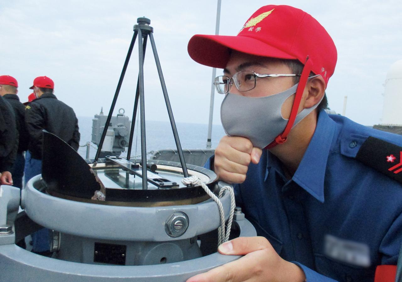 画像: 陸地の方位をもとに自艦の位置を測定する学生。海上自衛官としての知識経験を身に付けるため、護衛艦に乗艦し、艦艇勤務に関する実習を行う