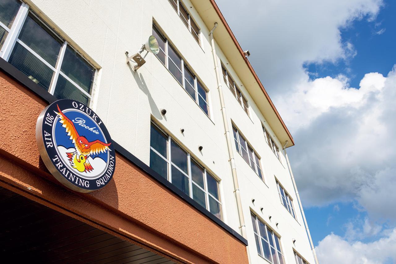 画像: ひなと、それを後ろから見守る荒鷲をシンボライズした第201教育航空隊のエンブレムが掲げられた庁舎。隊の任務を見事に表している