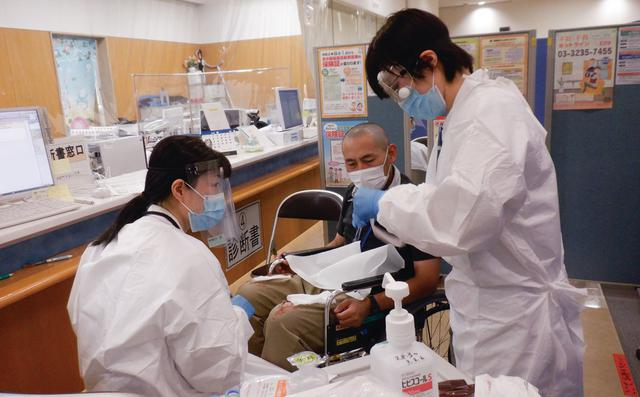 画像: 訓練では病院の待合室を使い、負傷者に応急処置を施す。負傷者役の服を破いたり、メイクでけがをリアルに再現