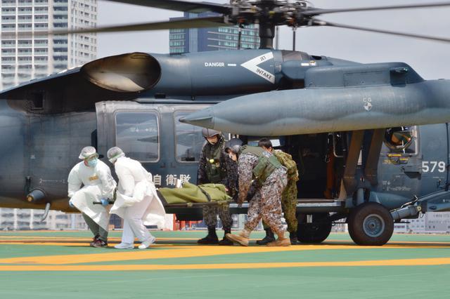 画像: 大量傷者受入訓練で、屋上のヘリポートより航空自衛隊の救難ヘリコプターUH-60Jから担架に乗せられた傷病者が運び出される