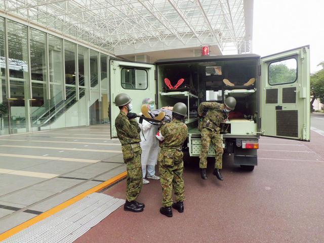 画像: 大規模スポーツイベント開催中に、テロが発生した想定で行われた20年の大量傷者受入訓練。現場近くでトリアージや応急処置を済ませた負傷者を、自衛隊の救急車に乗せて搬送する