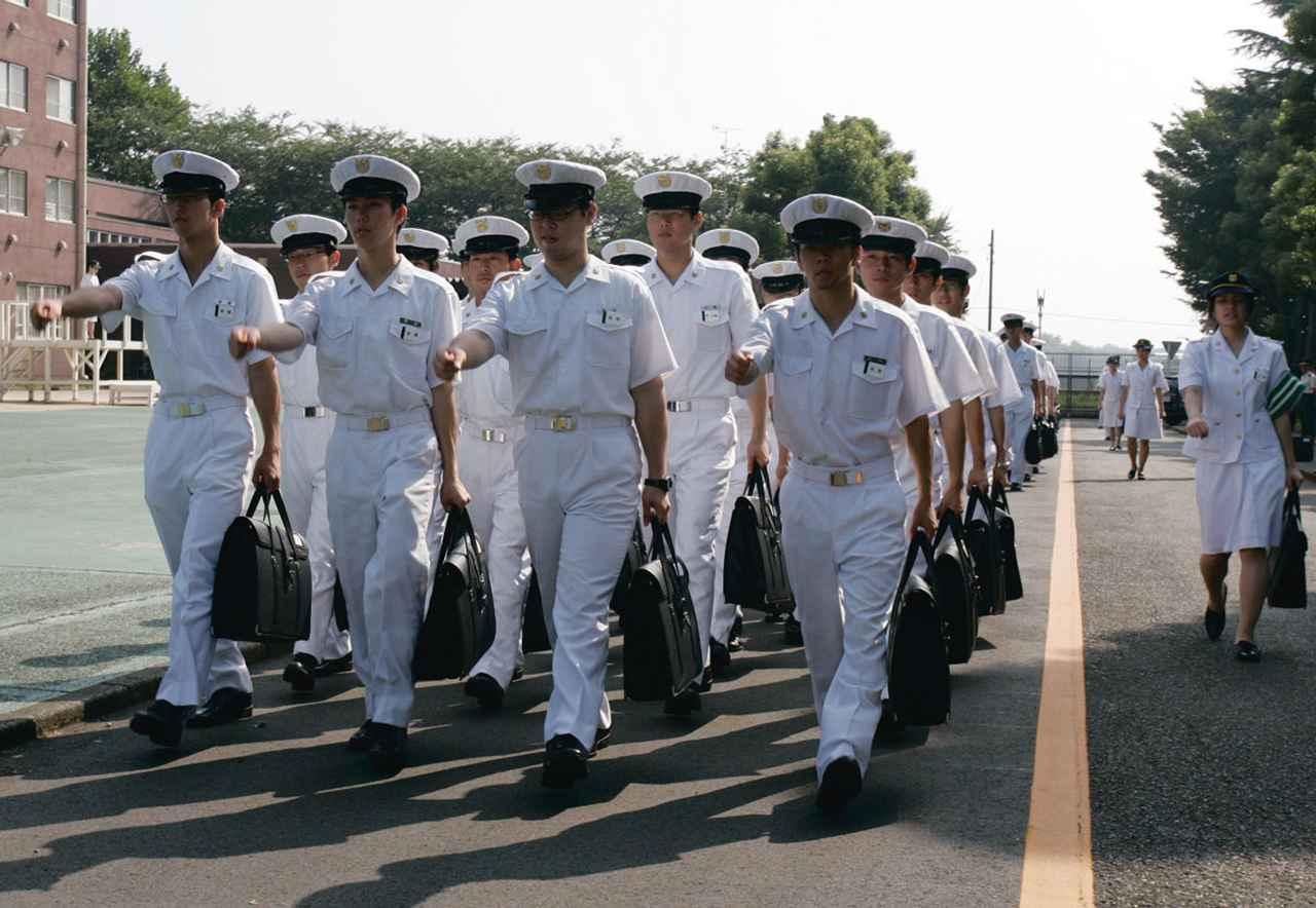 画像: 制服に身を包み、キャンパス内を行進する防衛医科大学校の学生たち。課業前は隊列を組んで整然と移動をする