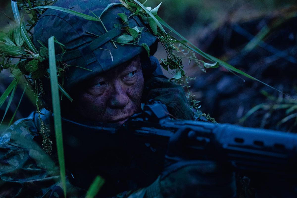 画像: 2夜3日にわたった演習で、最後の朝を迎えた田中予備陸士長。雨水のたまった陣地に潜み、雨、寒さ、疲労で消耗した体力を振り絞って攻撃部隊を警戒する