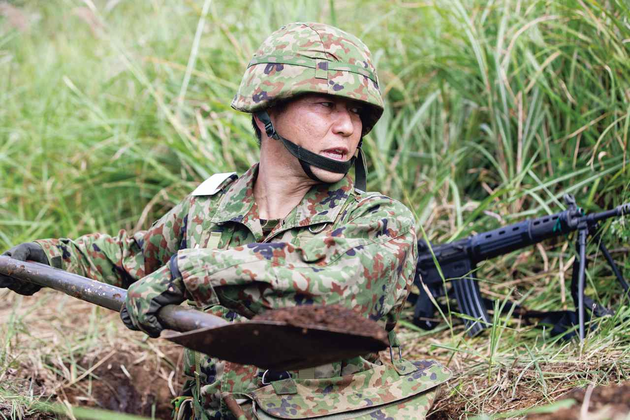 画像: 防御地域に到着し、小銃用の防御陣地を掘る田中予備陸士長。このほかにも、機関銃、対戦車火器といった装備に合わせ分隊員が協力して陣地を造る