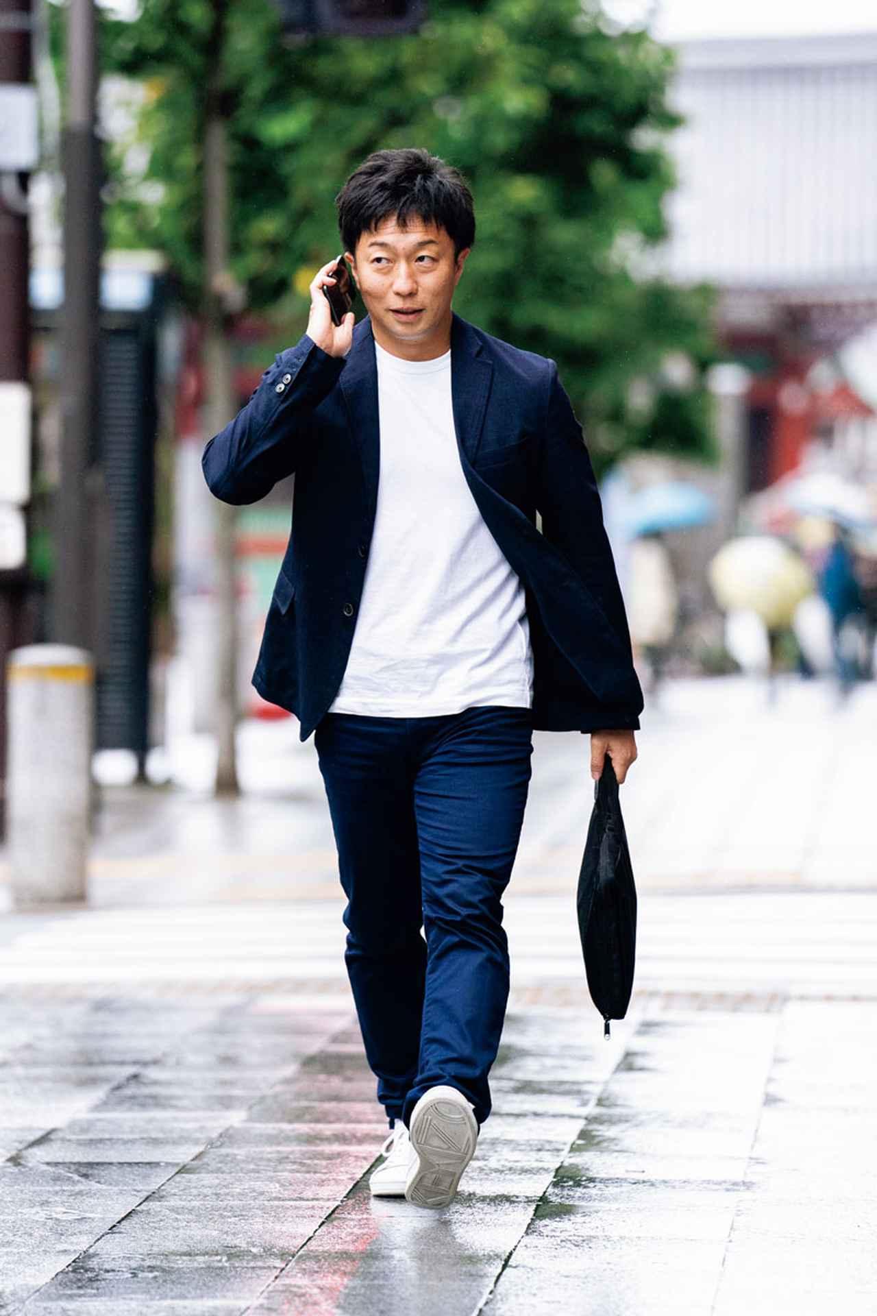 画像: 足早に勤務先に向かう田中さん。電話の応対をしながら歩く姿は、まさにビジネスマンだ