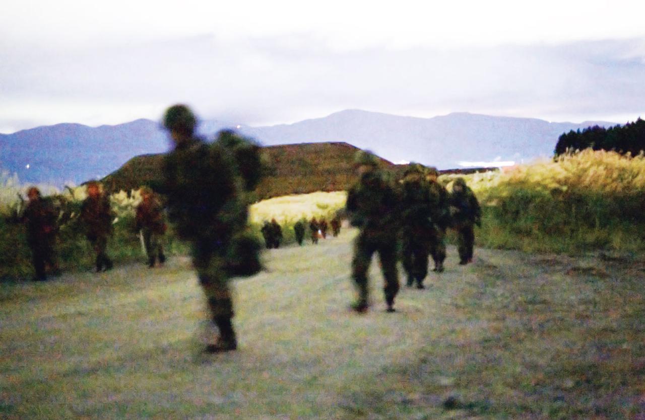 画像: 1日目の夜19時すぎから行進を続ける第1小隊。体力に不安のある一般公募予備自衛官を、常備自衛官らが励ましながら一体となって歩を進める(写真提供/防衛省)