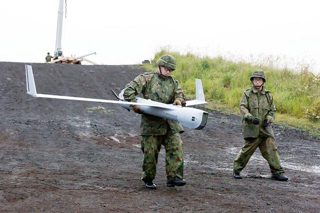 画像: 回収したスキャンイーグル2の機体を運ぶ隊員。破損の可能性もあるので、慎重に運ぶ