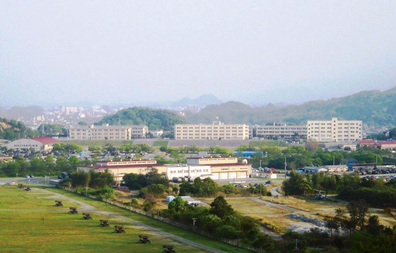 画像: 自然に囲まれた盆地にある飯塚駐屯地。写真手前の広場が訓練場で、その奥に整備工場、生活隊舎などが建ち並ぶ