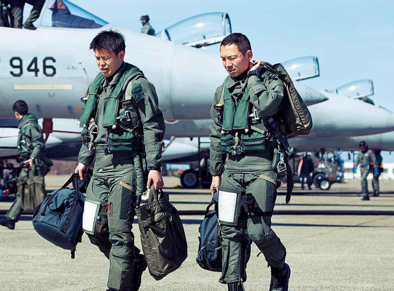 画像: 訓練を終え、並んで隊舎に戻るパイロット。このあとすぐに、訓練時の映像と飛行データをもとにしたレビューが行われる
