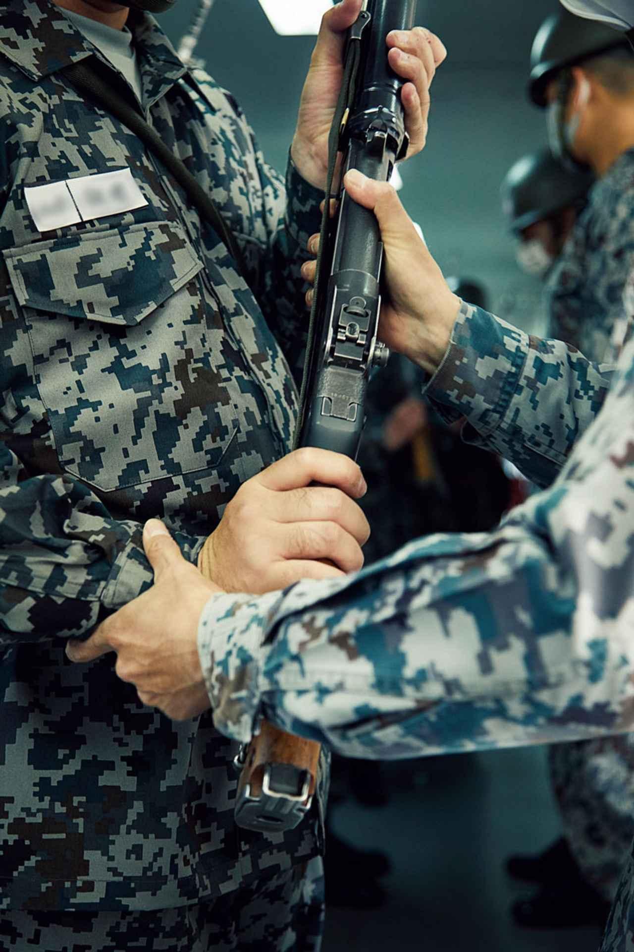 画像: 隊員が小銃を手にする際、教官は小銃に不備がないか責任を持って確認する