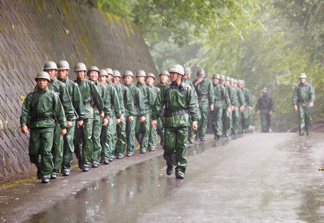 画像: 新入隊員の教育課程で行われる行進訓練。山岳地から市街地までの道のりを、隊列を組んで行進する 撮影/村上淳
