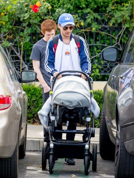 Louis Tomlinson smiles as he takes his son Freddie Reign for an afternoon stroll in Los Angeles, CA