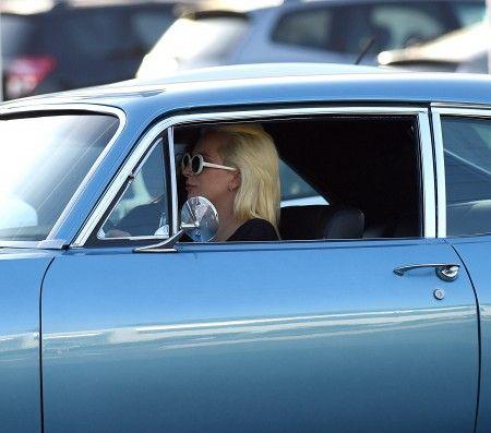 助手席に友人を乗せて車を運転するガガ。