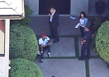 玄関前に座って警察の質問に答えるクリス。