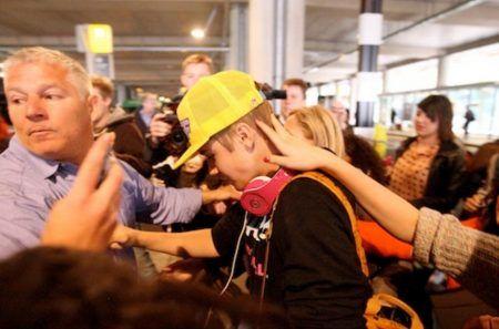 画像: この時の担当ボディガードの男性が必死に彼を守ろうとするも、ファンたちは手を伸ばし、服を引っ張るなどしてなんとかジャスティンに触れようとしている。
